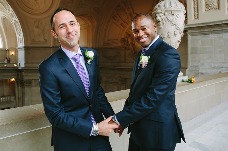 San Francisco City Hall wedding. Gay couple holding hands.