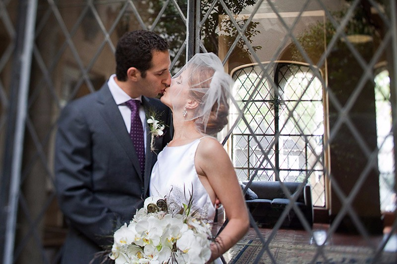 Groom kissing bride at their Berkeley City Club wedding. Orchid bridal bouquet, purple tie, veil fascinator