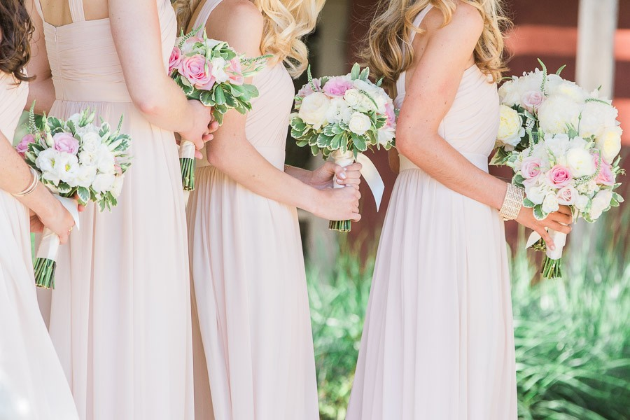 Bridesmaids in pale pink dresses with pink, white, and green floral bouquets at Bernardus Lodge Wedding
