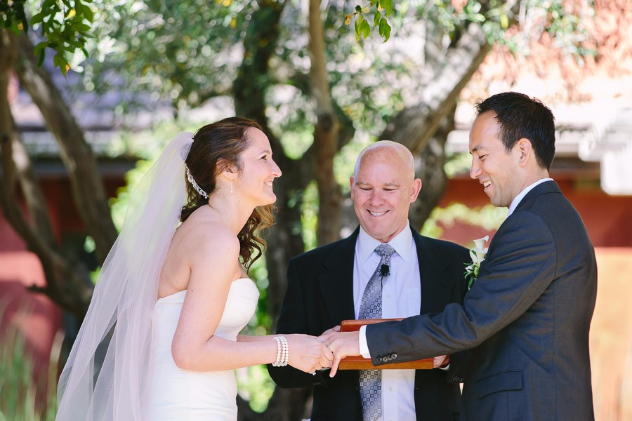 Bride places ring on groom's finger at Bernardus Lodge Wedding in Carmel