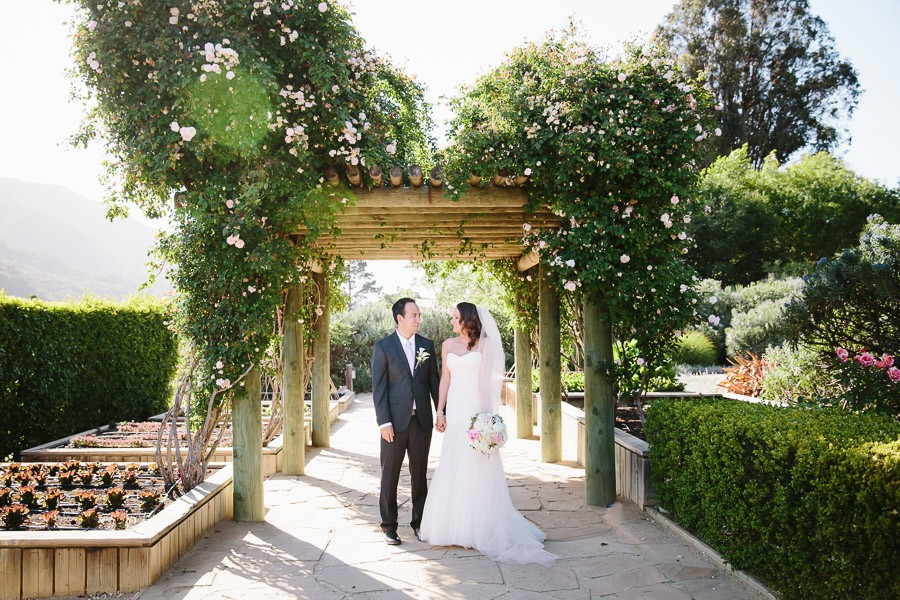 Bride and groom stand under the rose arbor at their Bernardus Lodge Wedding in Carmel