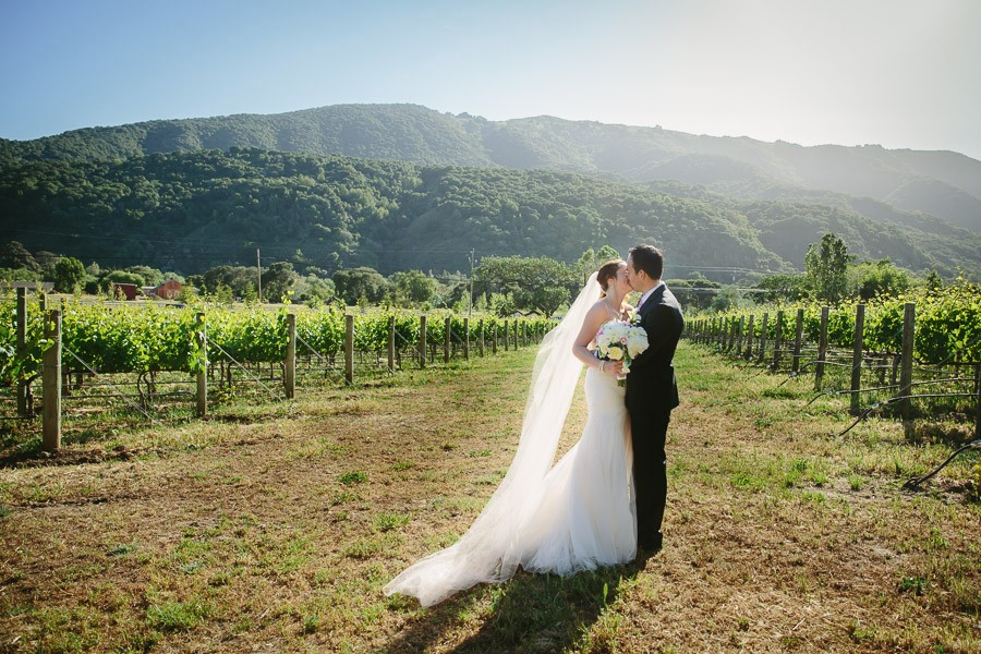 Bride and groom kiss in the vineyard at their Bernardus Lodge Wedding in Carmel