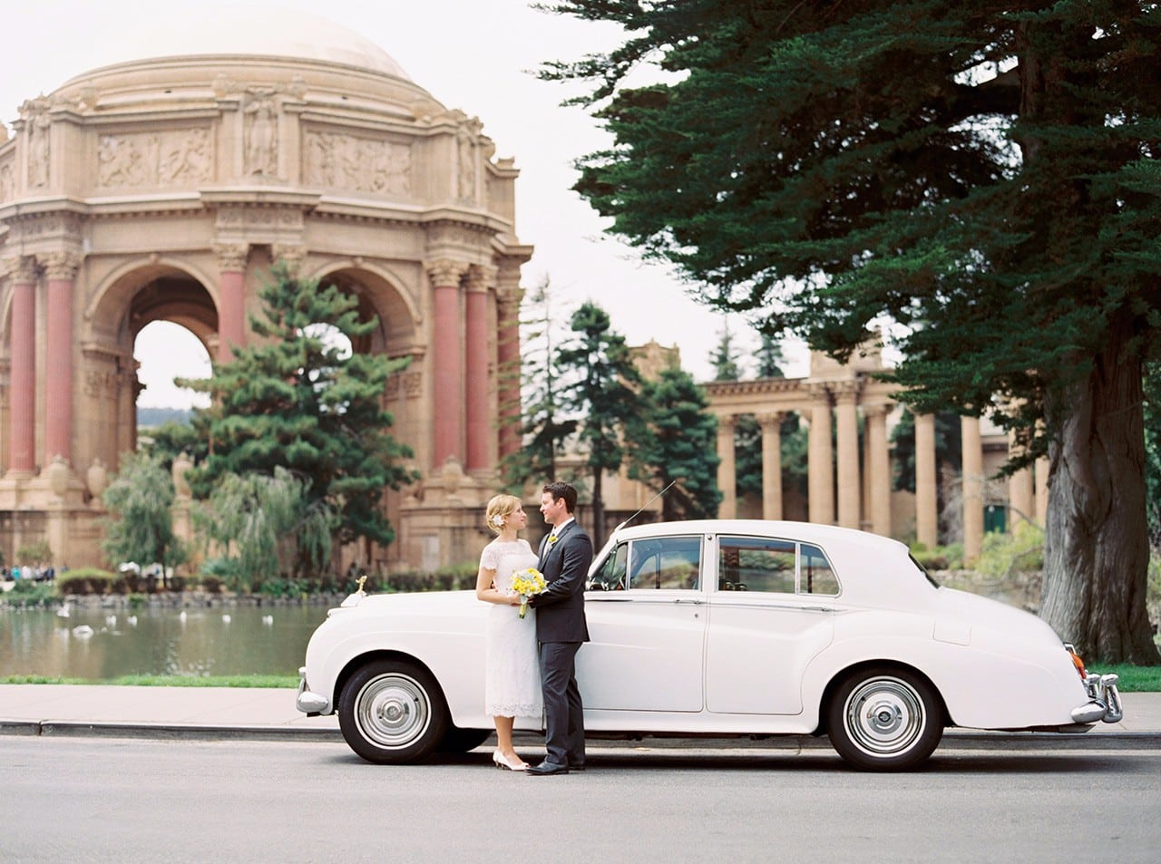 Bride and groom standing in front of a Rolls Royce at the Palace of Fine Arts in San Francisco