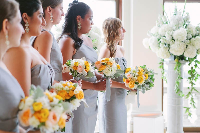 Bridesmaids holding yellow and white bouquets at a Flood Mansion San Francisco wedding. silver dresses. white hydrangeas