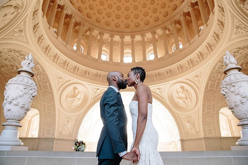 San Francisco City Hall wedding. Bride and groom kissing on Fourth Floor.