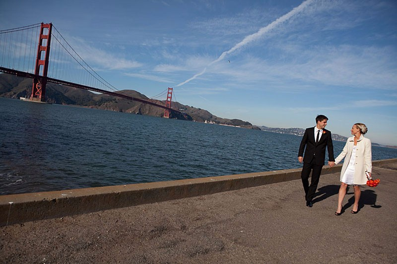 San Francisco City Hall wedding. Bride and groom walking on pier with Golden Gate Bridge in background.
