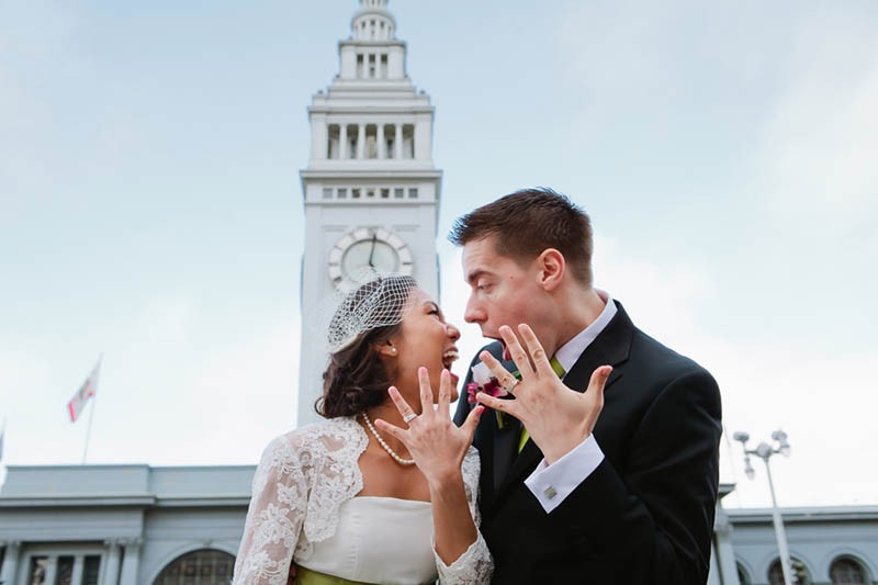 San Francisco City Hall wedding. Bride and groom standing in front of the Ferry Building.