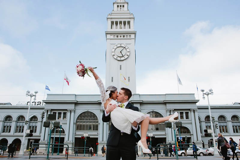 San Francisco City Hall wedding. Groom lifting bride in front of the Ferry Building.