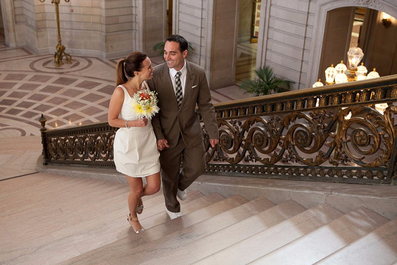 San Francisco City Hall wedding. Bride and groom walking on the Grand Staircase.