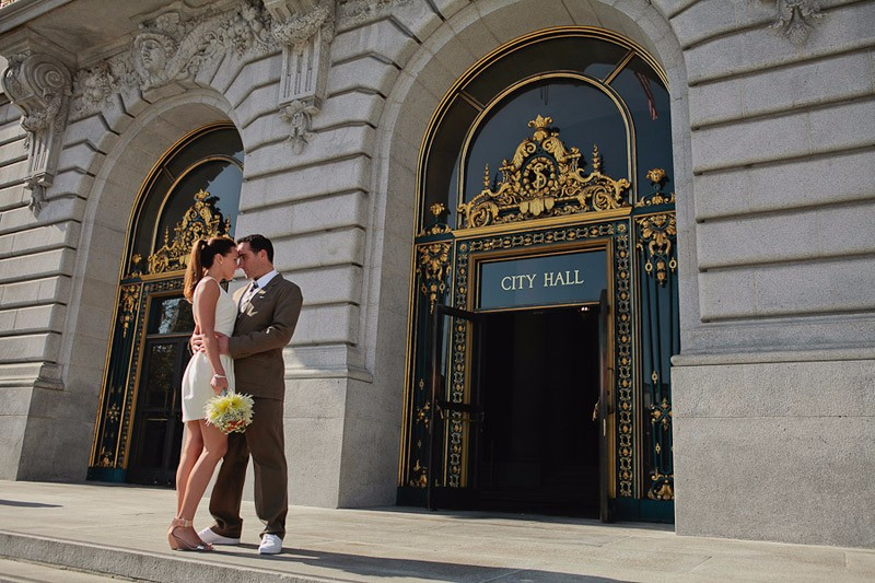 Bride and Groom standing in front of the doors at SF City Hall. elopement