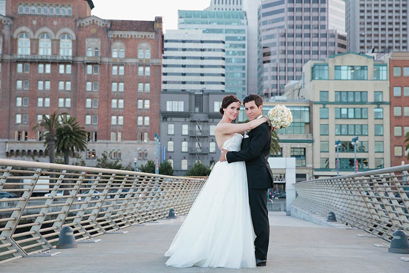San Francisco City Hall wedding. Bride and groom walking on Pier 14.