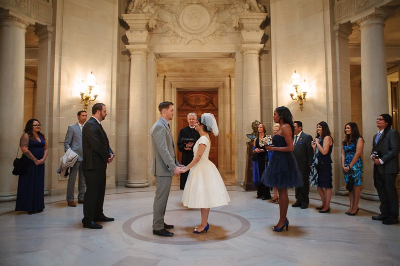 Bride and groom surrounded by their friends and family during the ceremony in the rotunda of San Francisco City Hall