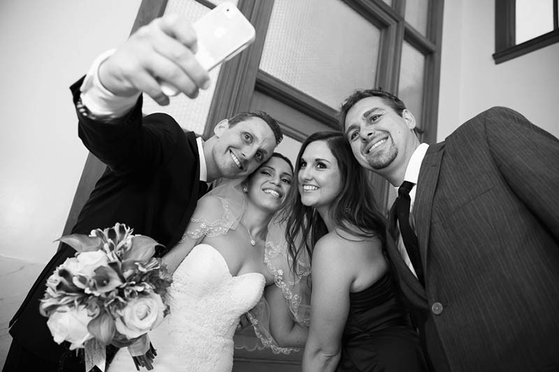 San Francisco City Hall wedding. Bride and groom take selfie with friends.