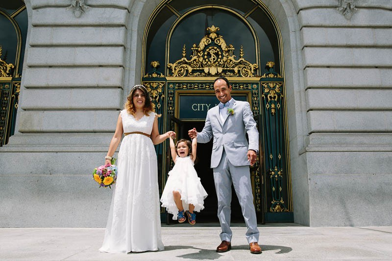 San Francisco City Hall wedding. Bride and groom pose with their daughter after getting married.