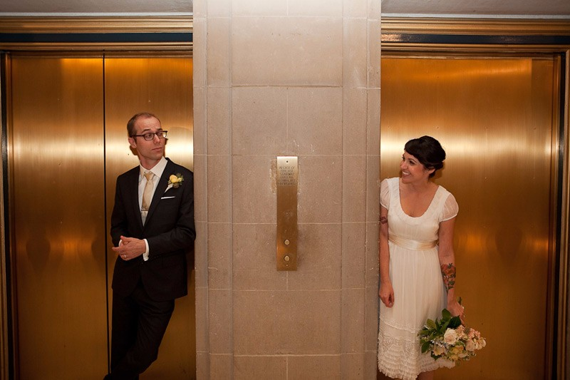 Bride and groom standing in front of the elevators at SF City Hall