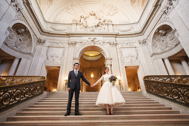 San Francisco City Hall wedding. Bride and groom standing on Grand Staircase.