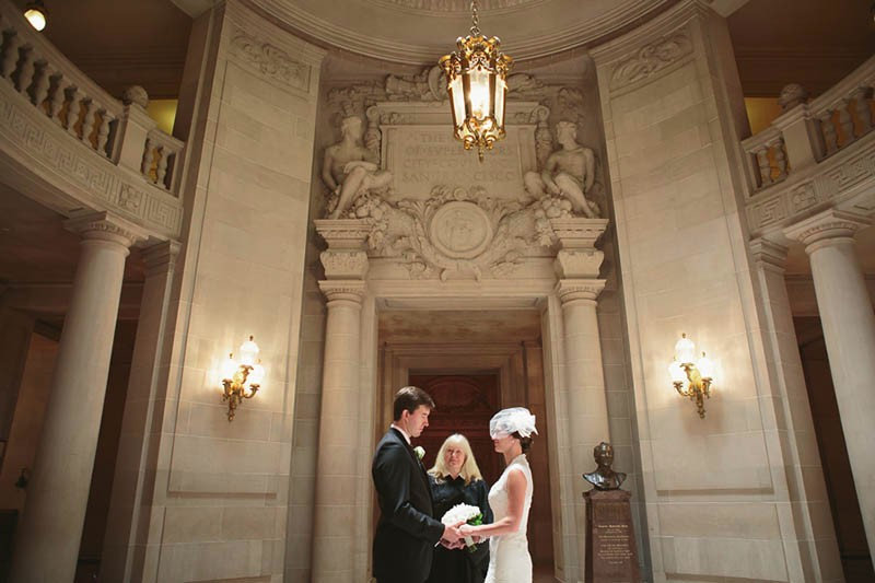 San Francisco City Hall wedding. Bride and groom during their ceremony in the Rotunda.