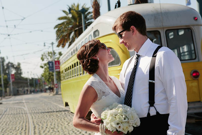 San Francisco City Hall wedding. Bride and groom standing in front of a trolley on the Embarcadero.
