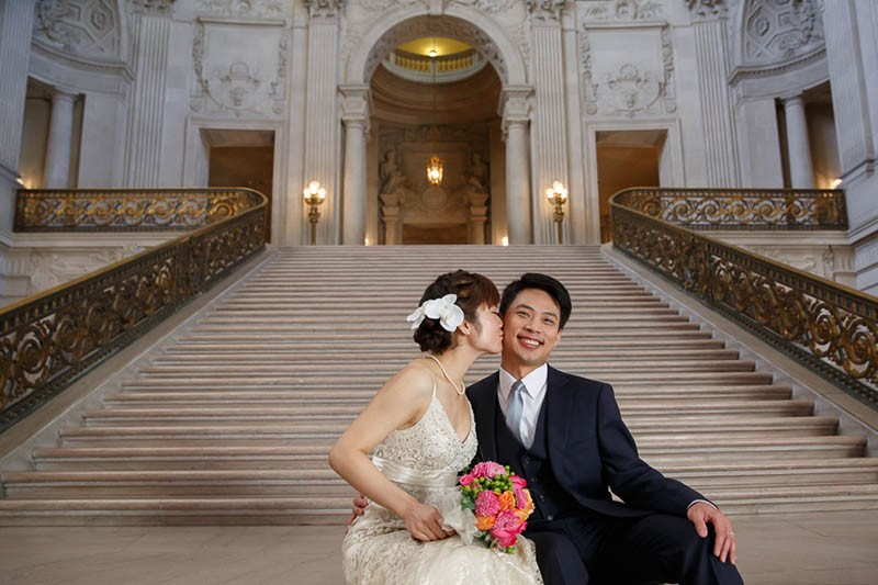 Bride kissing the groom's cheek while sitting on the Grand Staircase inside SF City Hall
