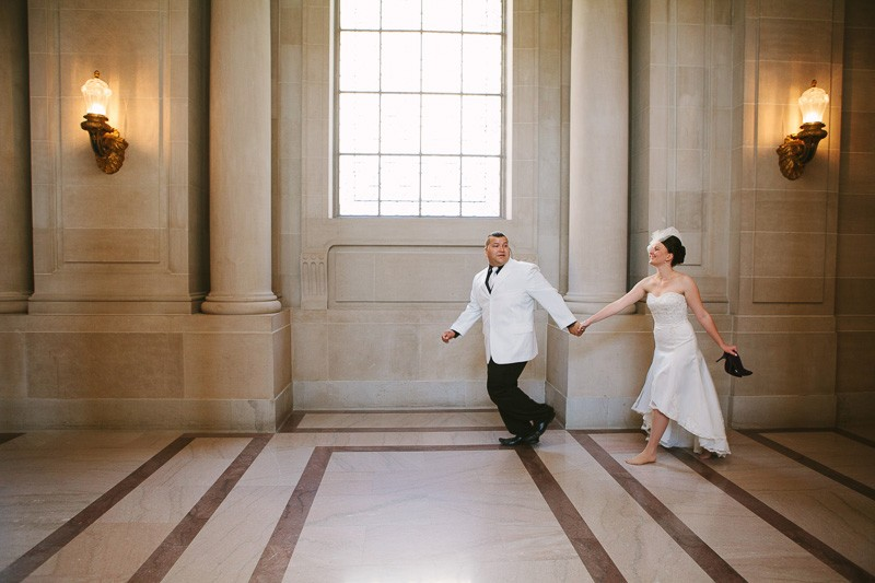 San Francisco City Hall wedding. Bride and groom running together.
