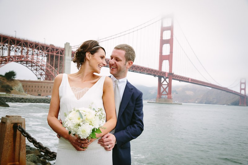 San Francisco City Hall wedding. Bride and groom standing in front of the Golden Gate Bridge.
