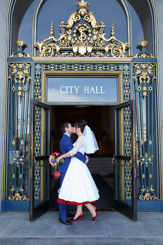 Bride and groom kissing at front door after their San Francisco City Hall wedding