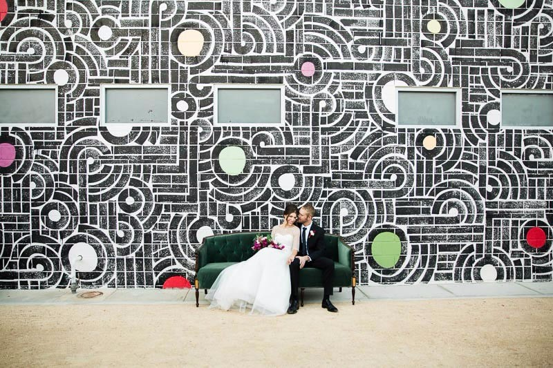 Bride and groom sitting on sofa in front of a colorful mural at their Ace Hotel Palm Springs wedding