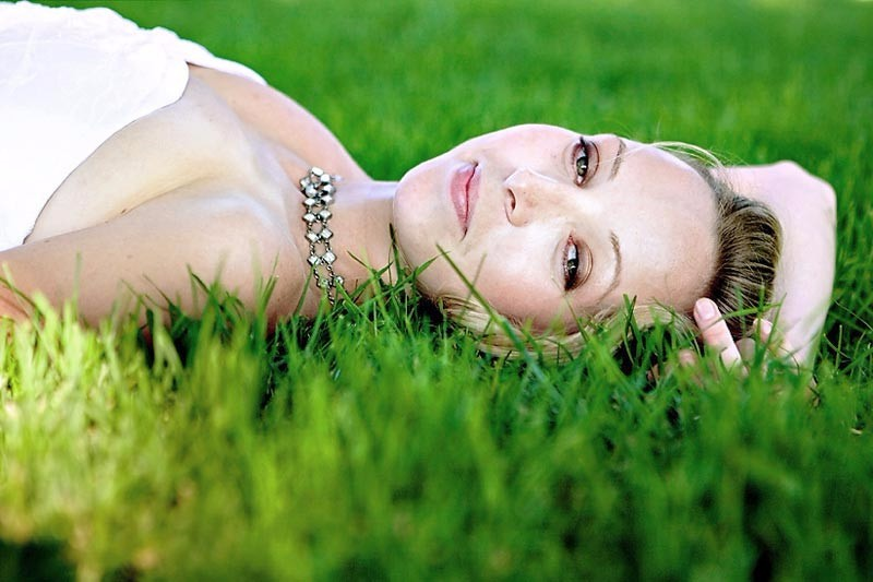 Bride laying on grass in San Francisco wedding