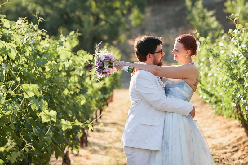 Bride and groom standing in a vineyard after their Sonoma wedding