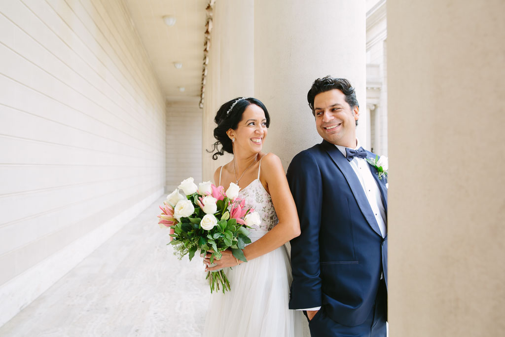 San Francisco City Hall Wedding Photographer. Bride and groom at the Legion of Honor after their City Hall wedding. pink and white bridal bouquet. Navy blue tuxedo for groom.